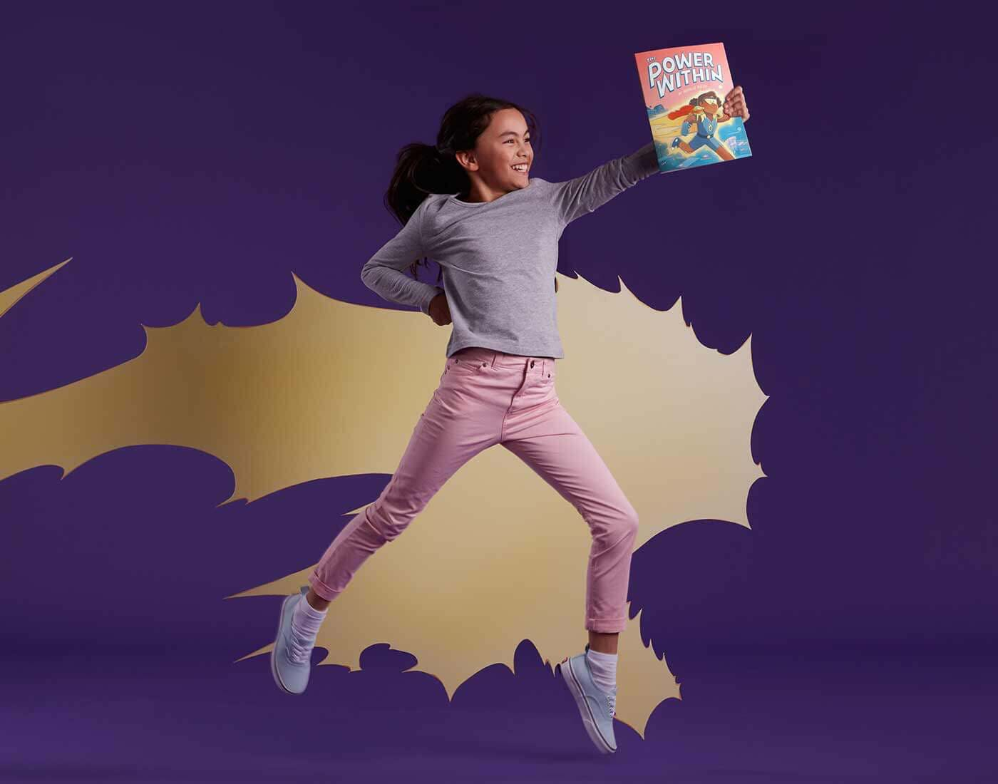 Child holding The Power Within book leaping through the air as an empowered super hero